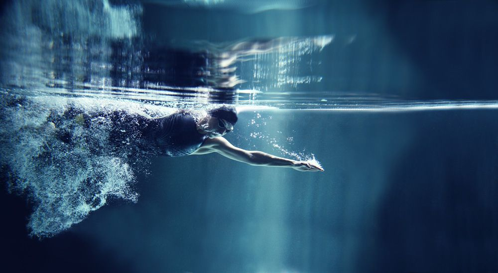 professional swimmer crawl underwater isolated blue background