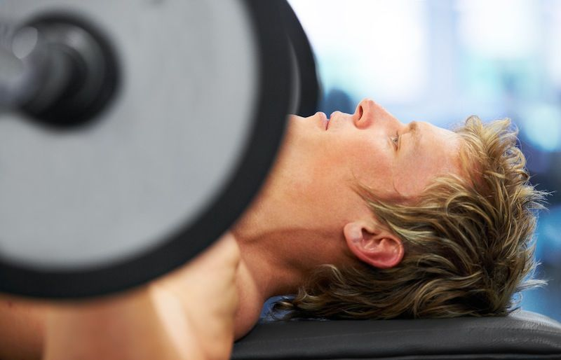 Closeup profile of a man exercising on the bench press